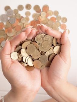 女性の手の中にたくさんのコイン