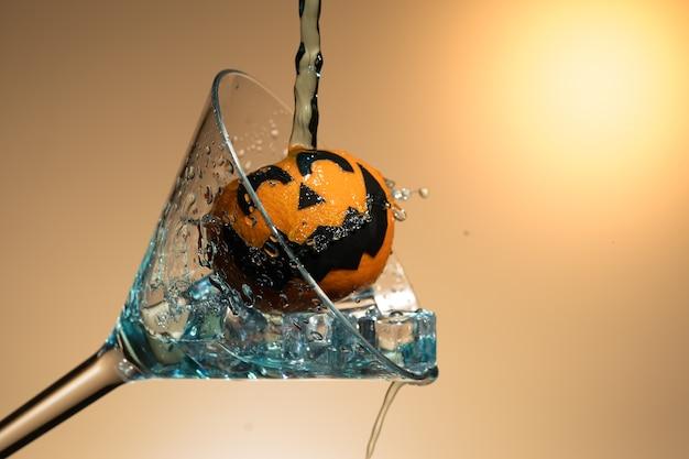 氷とスプラッシュのマティーニのガラスのカボチャの顔とオレンジ。