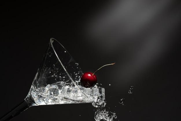 Закройте вид брызг воды с падающей вишни.
