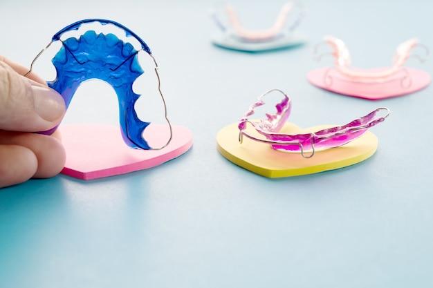 青い背景の歯科用リテーナ歯列矯正器具。
