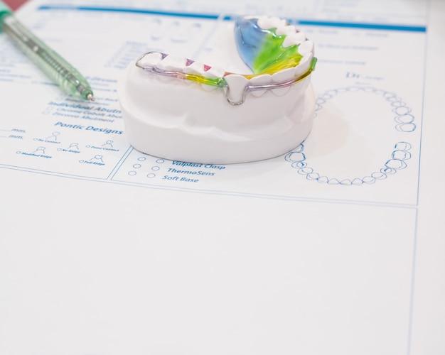 カラー背景の歯科用リテーナ歯列矯正器具。