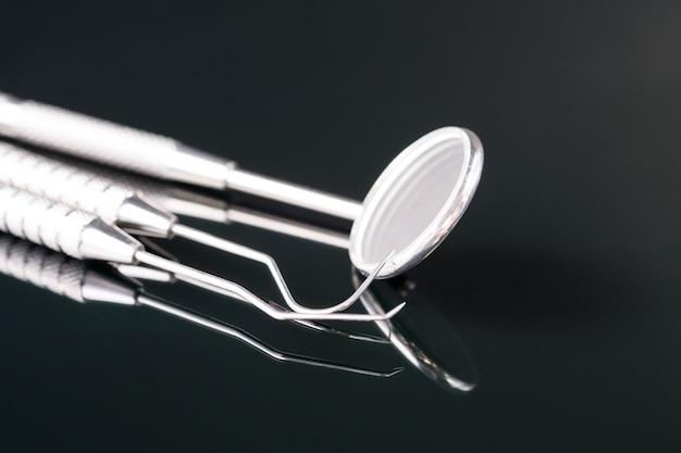 歯科用具はオフィスまたは医院の歯科医のために使用します。黒い背景に。
