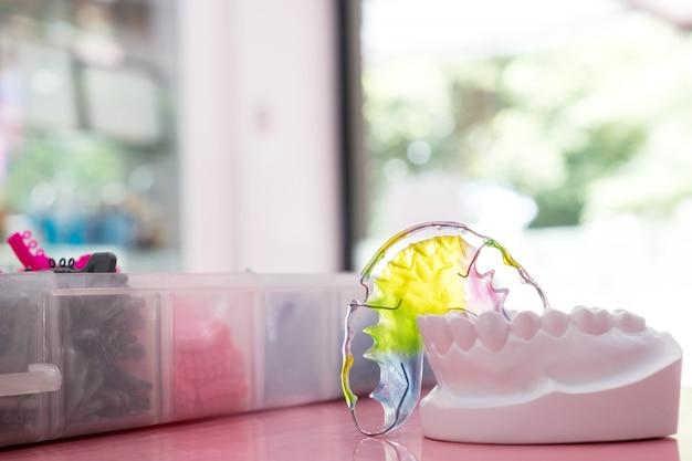 色の背景上の歯科用リテーナー矯正器具