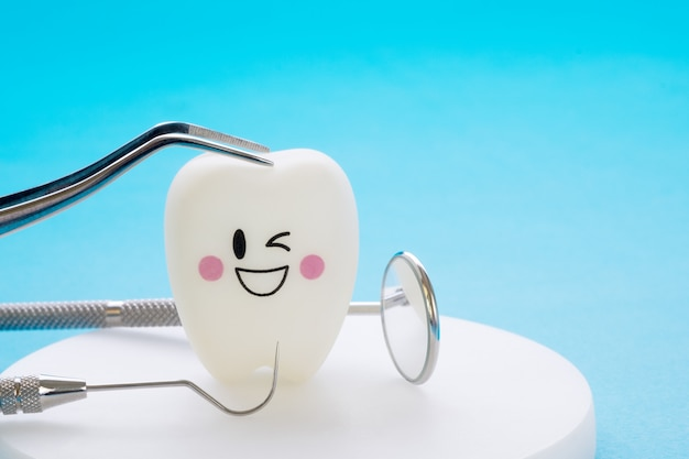 青色の背景に歯科用ツールと笑顔歯モデル。