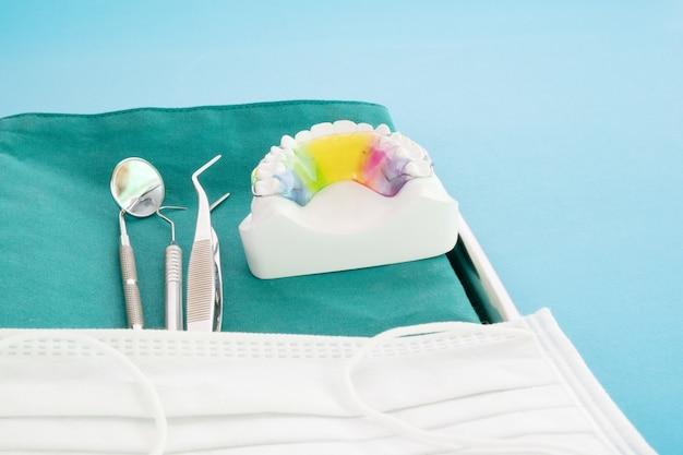 歯科用リテーナー矯正器具と青色の背景に歯科用ツール。