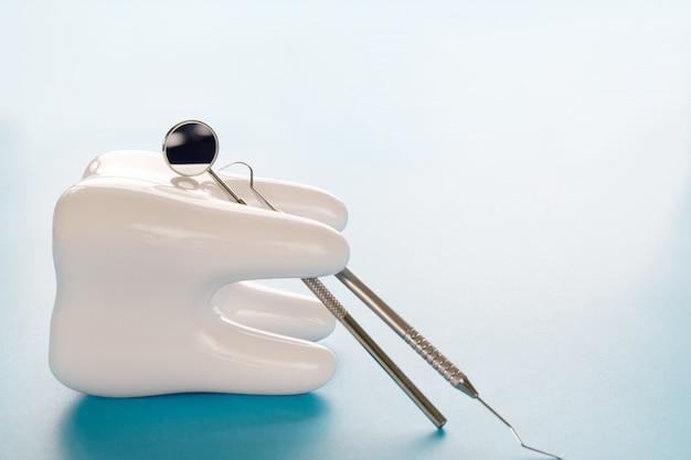 青い背景に大きな歯と歯医者のツール。