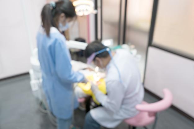 歯科医と彼のアシスタントのぼやけた画像写真はクリニックで働いています。