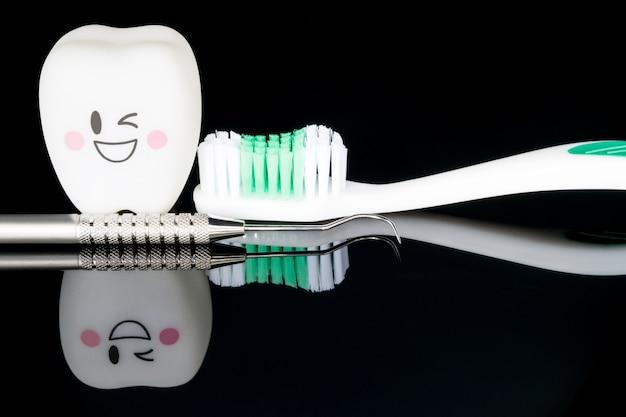 黒の背景に歯科用ツールと笑顔の歯のモデル。