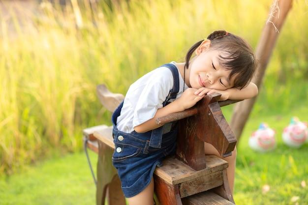 Азиатская девочка маленькая девочка, верхом на деревянной лошади игрушка в саду зеленой травы.