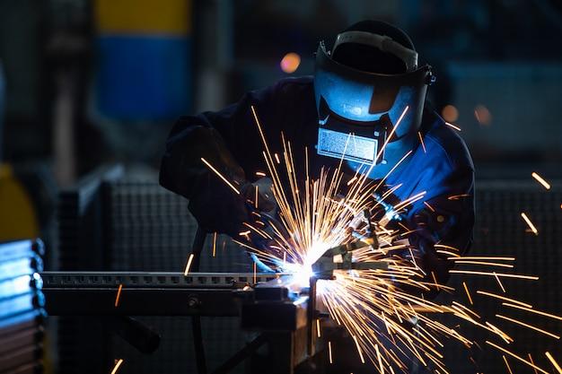 Рабочие в промышленных униформах и сварочной маской на заводах по сварке стали.