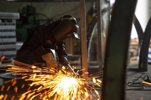 工場内の複数のスパークを伴う鉄骨構造物および溶接機の電気ホイール研削。