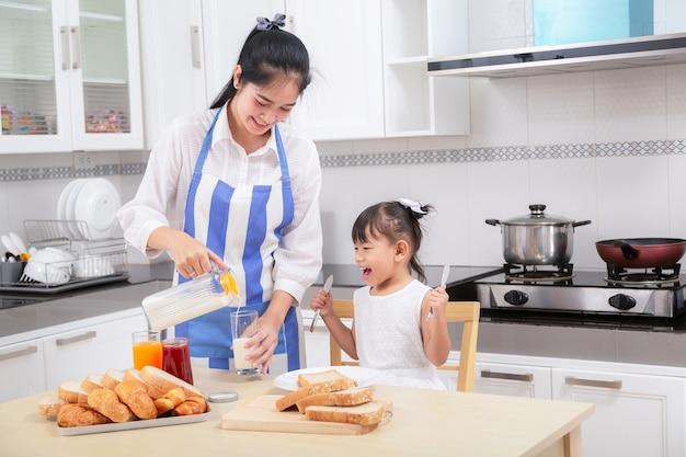 家族の朝食の準備。アジアの母親と赤ちゃんの娘が朝食を朝に調理する。