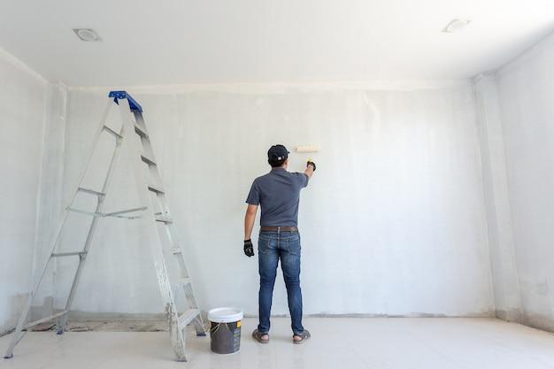 Художник за работой с красящим роликом на стене