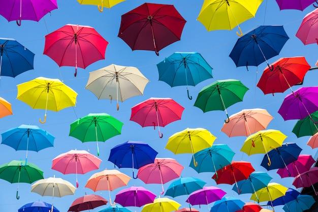 カラフルなパラソルの背景。空にカラフルな傘。