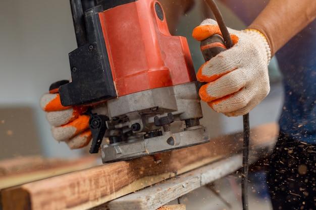 研磨機で家具部品を処理するカーペンター。ボード上のグラインダー。