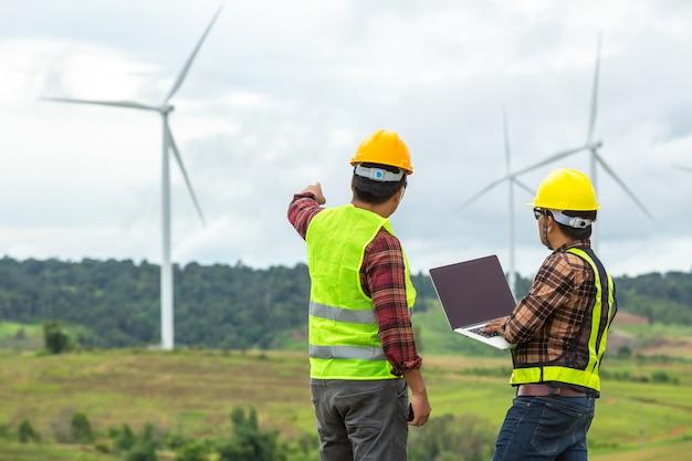 Два ветряная мельница инспекции и проверки прогресса ветротурбины на строительной площадке.