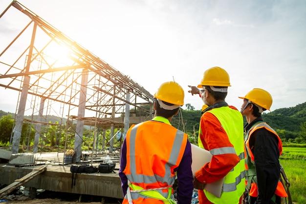 安全服を着ている建設労働者の労働者制御のチームを見て、建設現場で議論する建設現場でオフィスのラップトップをチェックするエンジニア技術者。