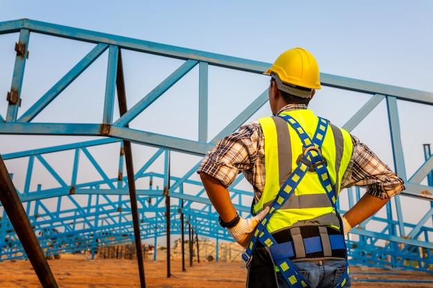 建設現場の高さ機器での作業。セレクティブフォーカスの安全ボディハーネスのフックを持つ労働者のための落下防止装置。