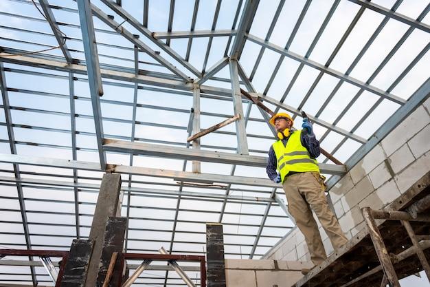 建設エンジニアは家の鋼鉄屋根構造を建設しています。家の建設のコンセプトです。