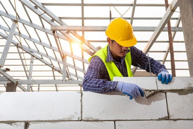 Каменщик-строитель работает с автоклавными газобетонными блоками. облицовка стен, укладка кирпича на стройке, инженерные и конструкторские решения.