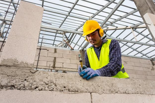 建設労働者は、ハンマーを使用してコンクリートの釘を軽量のコンクリートブロックに打ち込み、家を建てます。
