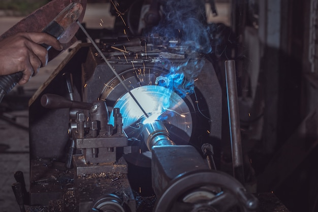 Крупный план профессиональный сварщик в защитной форме и защитной металлической сварочной металлической трубе на промышленном столе позади промышленного предприятия.