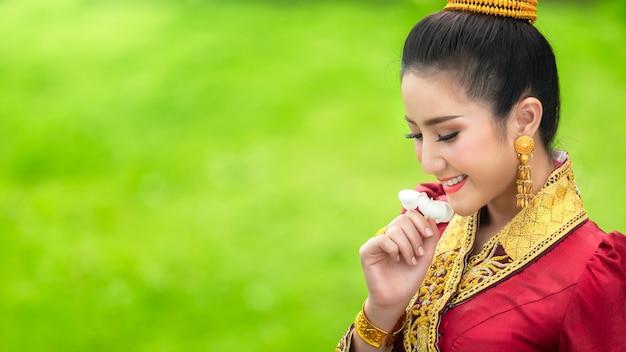 ラオスの国花、チャンプ花と伝統的なドレスでラオスの女の子の顔。