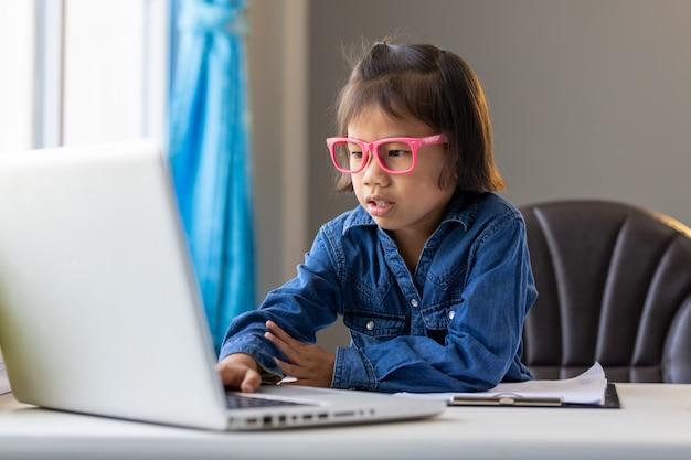 アジアの若い女の子はオンラインで勉強して家にいます病気の状況で