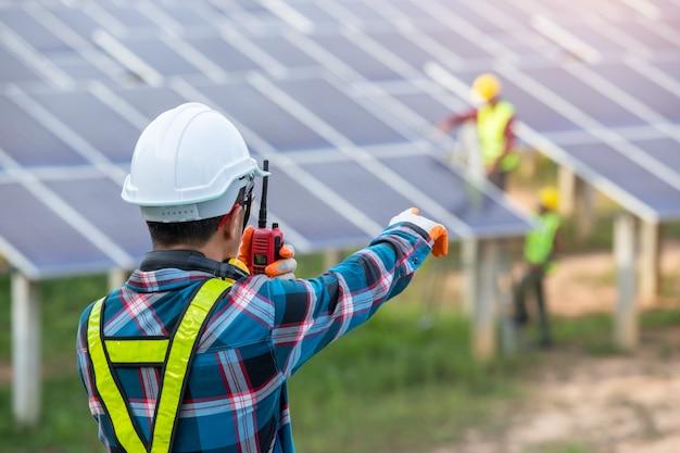 Азиатский инженер работает над проверкой оборудования на солнечной электростанции, чистой энергии, возобновляемых источников энергии