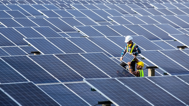 太陽光発電、純粋なエネルギー、再生可能エネルギーの機器のチェックに取り組んでいるアジアのエンジニア