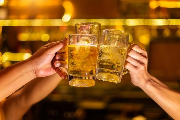 Группа счастливых друзей, пьющих и поджаривающих пиво в пивоварне-баре-ресторане