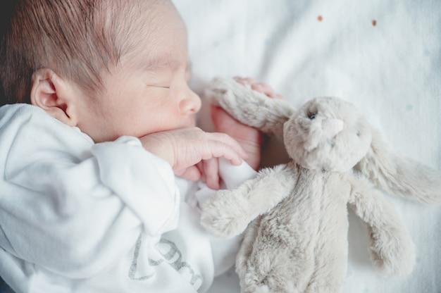 小さなウサギとベッドで寝ている生まれたばかりの赤ちゃん。家族と愛の概念。アジアの子供。