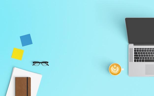 コーヒーカップ、ノートブック、白紙の紙と青い色のラップトップでモダンなワークスペース