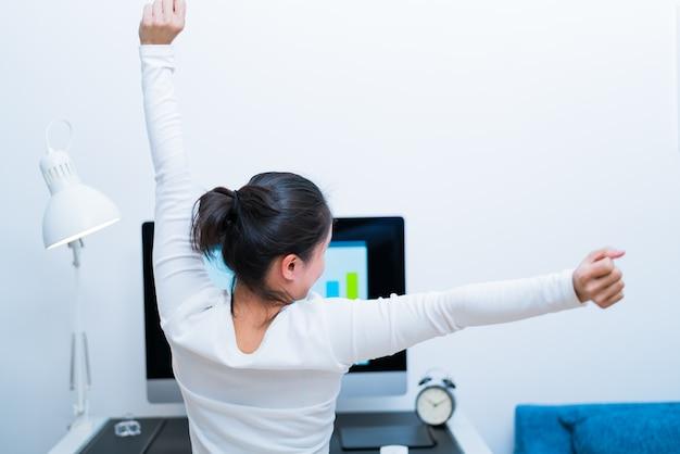 После долгой работы женщина растягивается. без стресса и отдыха