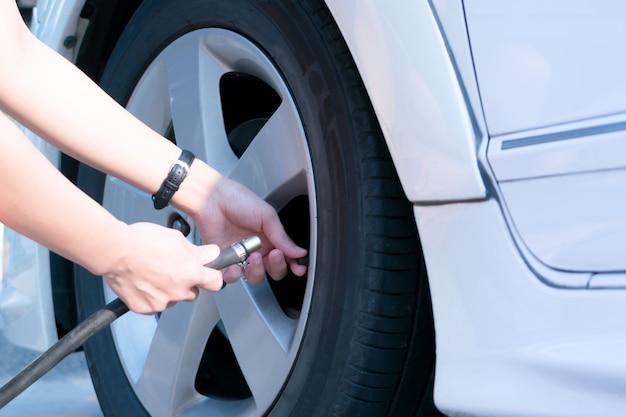 Водитель наполняет воздух автомобильной шиной, накачивает