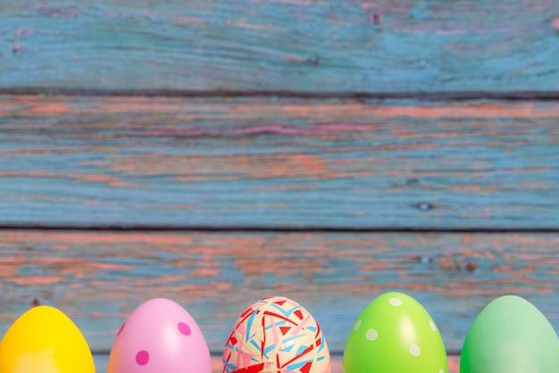 青い木製の背景、休日の装飾で立っているハッピーイースターの卵