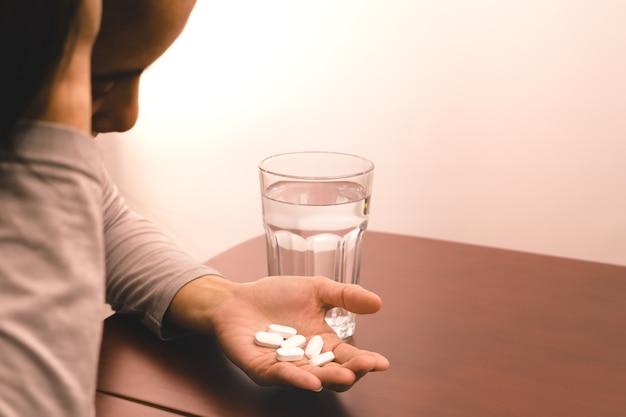 頭痛の女性の手は水のガラスで薬を握って