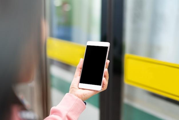 若い女性がスマートフォンでオンラインショッピング。事業コンセプト