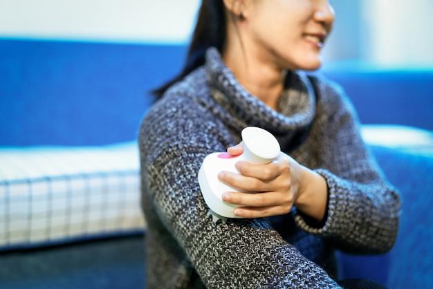 女性の腕の上でリラックスしてマッサージ、電気腕、首と肩のマッサージ機