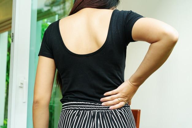 Боль в спине у себя дома. женщины страдают от боли в спине. здравоохранение и медицинская концепция