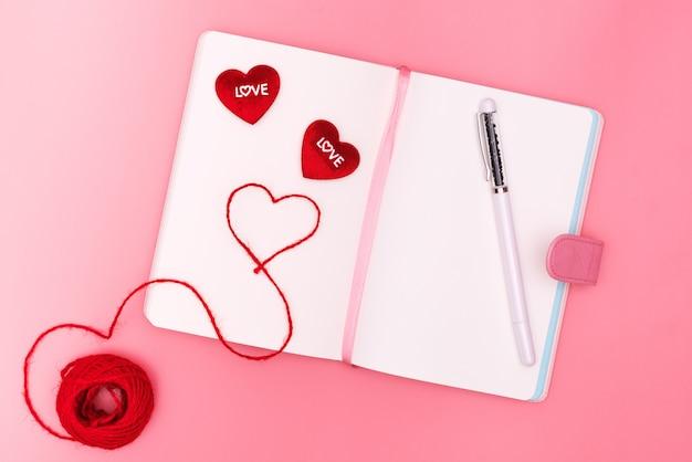バレンタインデーのコンセプト、ピンクの背景に赤いハートの愛を毎日