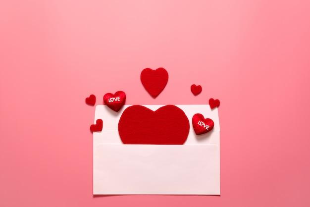バレンタインデーのコンセプト、ピンクの背景に赤いハート白封筒