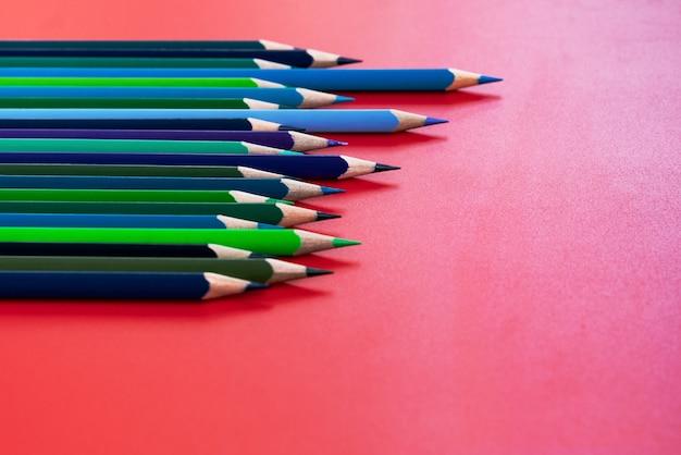 チームワークの概念赤の背景に色鉛筆のグループ