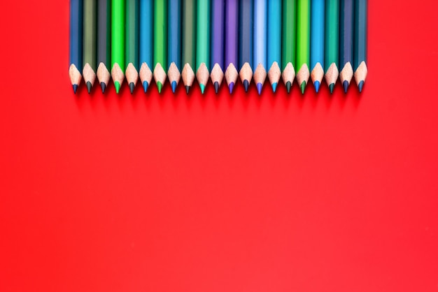 多様性の概念赤の背景にミックス色鉛筆の行