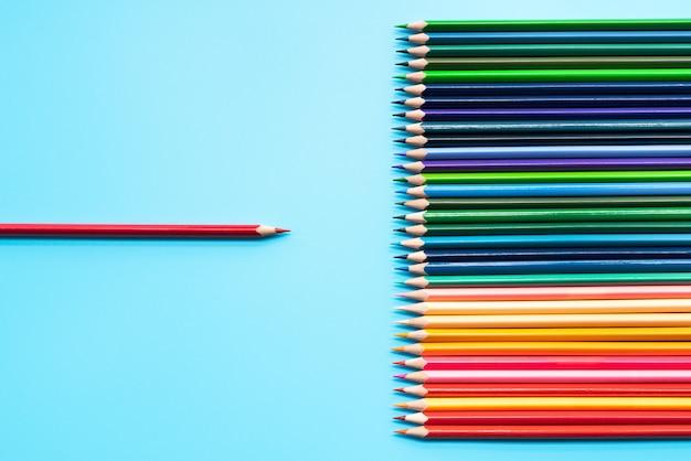 リーダーシップのビジネスコンセプトです。他の色への赤い色鉛筆によるプレゼンテーション