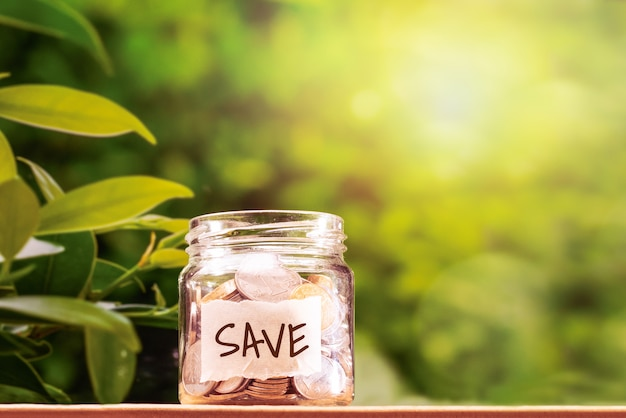 お金を節約、お金を節約するためのガラスの瓶にコイン