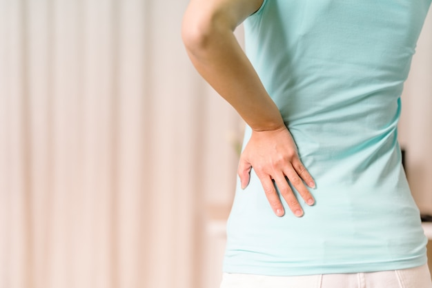 自宅で腰痛。女性は腰痛に苦しんでいます。ヘルスケアと医療の概念