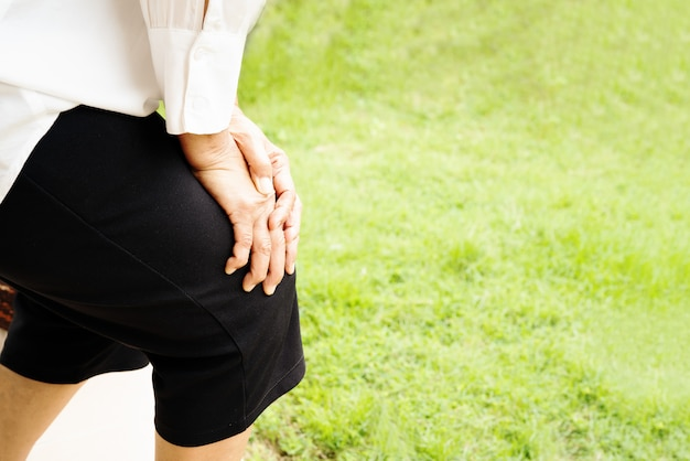 健康問題の概念、自宅で膝の痛みに苦しんでいる年配の女性