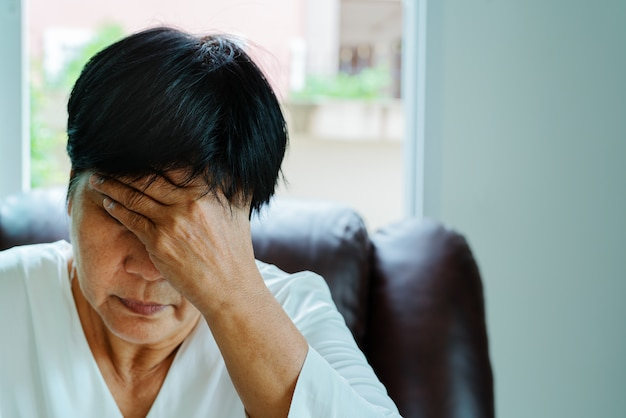 頭痛、ストレス、片頭痛、健康問題の概念に苦しんでいる老婦人