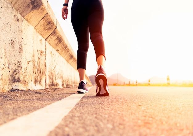 スポーツ女性は道端に向かって歩きます。ステップの概念